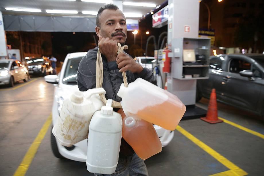 Homem carrega galões com gasolina em posto de combustível em Brasília - 26/05/2018
