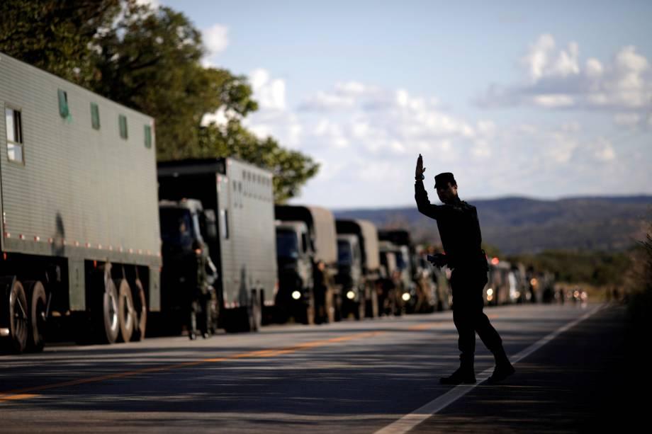 Oficial militar acena para caminhões do Exército na rodovia GO-010 em Goiás - 26/05/2018