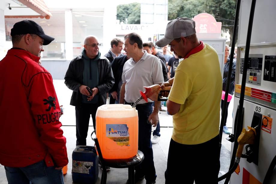 Pessoas enchem galões de gasolina durante a paralisação de caminhoneiros em um posto de combustível em Curitiba (PR) - 26/05/2018
