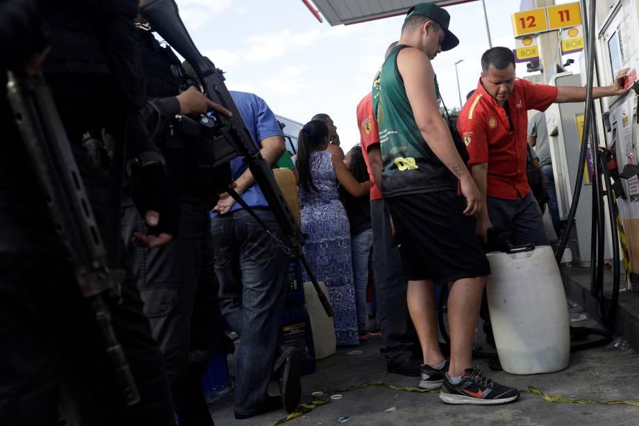 Policiais patrulham enquanto pessoas enchem vasilhas com gasolina em um posto de combustível no Rio de Janeiro - 28/05/2018