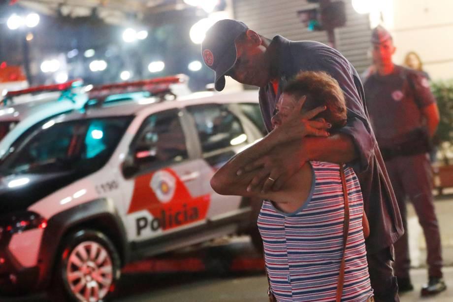 Bombeiro tenta confortar uma mulher durante incêndio em um edifício ocupado por moradores sem-teto no Largo do Paissandu, no centro de São Paulo - 01/05/2018