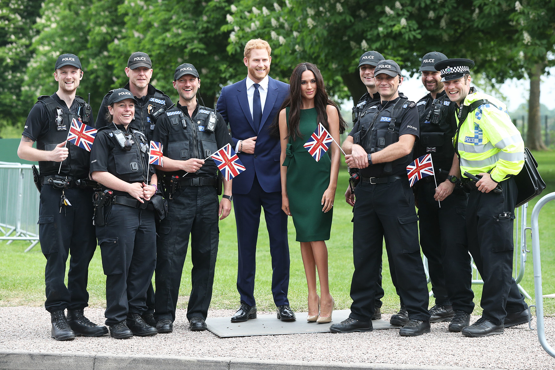 Policiais posam para fotos com as estátuas de cera do príncipe Harry e da atriz Meghan Markle, nos arredores do Castelo de Windsor - 16/05/2018