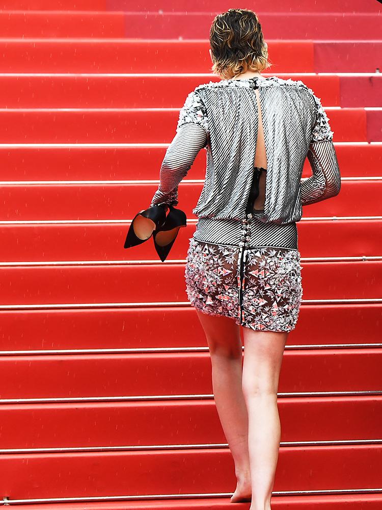 A atriz Kristen Stewart caminha descalça no tapete vermelho do Festival de Cannes, na França - 14/05/2018