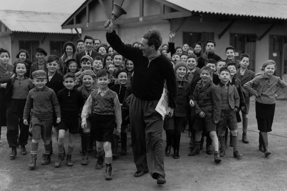 Líder de acampamento guia as crianças anunciando a hora do lanche - 11/01/1939