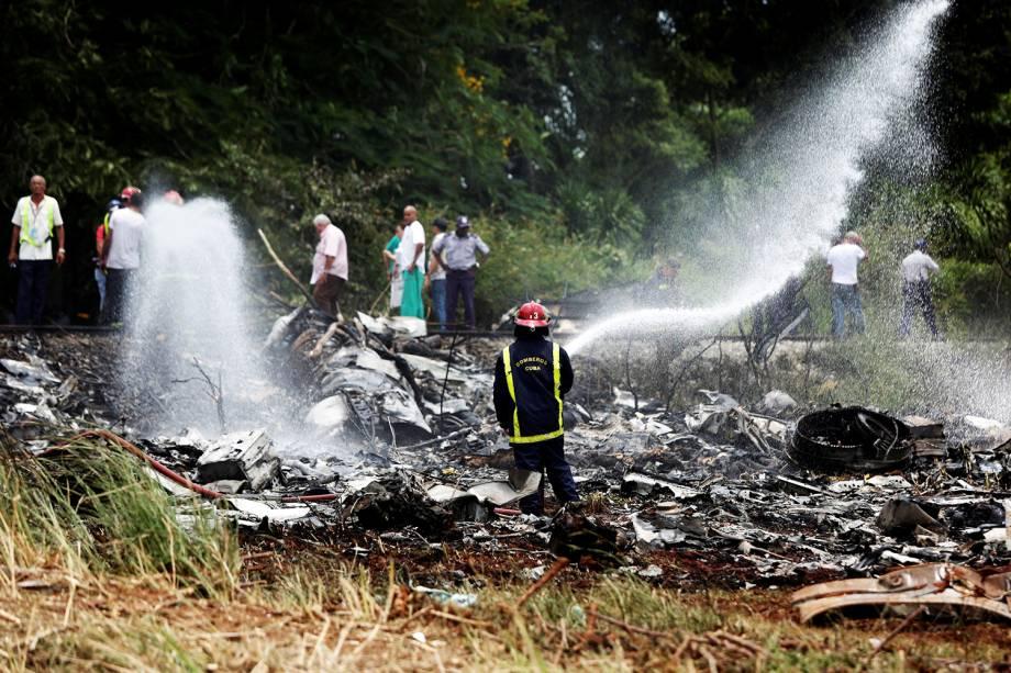 Bombeiro realiza trabalho de rescaldo após avião cair depois de decolar em Havana  - 18/05/2018