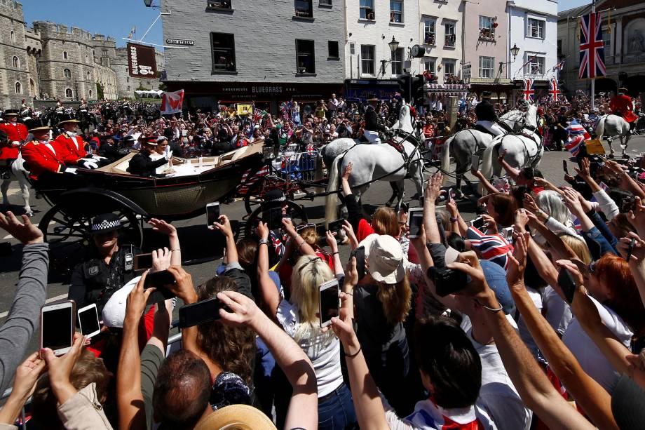 Espectadores aplaudem quando o príncipe Harry e sua esposa, Meghan Markle, montam uma carruagem depois de sua cerimônia de casamento na capela de São Jorge em Windsor - 19/05/2018
