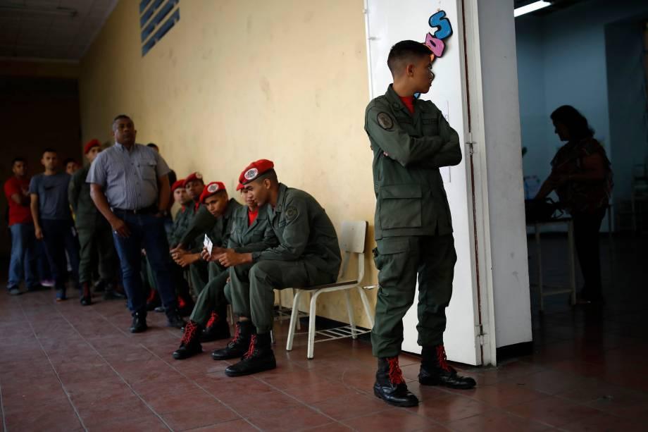 Soldados e civis venezuelanos esperam para votar em um centro de votação durante a eleição presidencial em Caracas - 20/05/2018