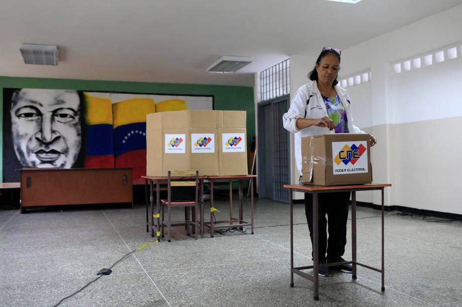 Com uma imagem do falecido presidente venezuelano, Hugo Chávez ao fundo, cidadã venezuelana vota durante a eleição presidencial em Caracas - 20/05/2018