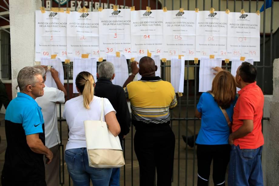 Cidadãos venezuelanos checam listas eleitorais em uma seção eleitoral durante a eleição presidencial em Caracas - 20/05/2018