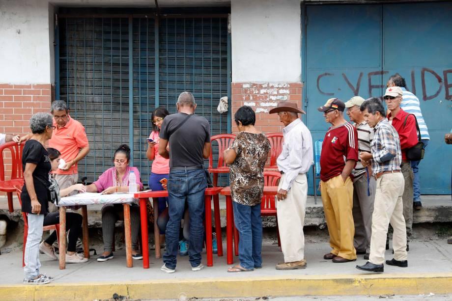 """Cidadãos venezuelanos fazem check-in em um """"ponto vermelho"""",  área criada pelo partido do presidente Nicolás Maduro, para verificar se eles votaram durante a eleição presidencial em Barquisimeto - 20/05/2018"""