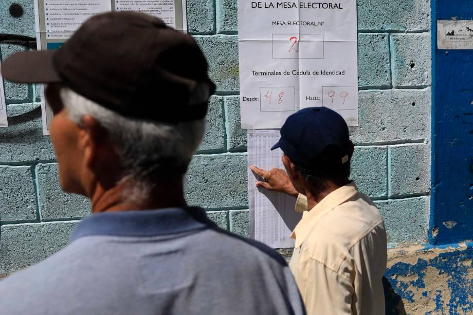 Cidadãos venezuelanos checam listas eleitorais em um centro de votação durante a eleição presidencial em Caracas - 20/05/2018