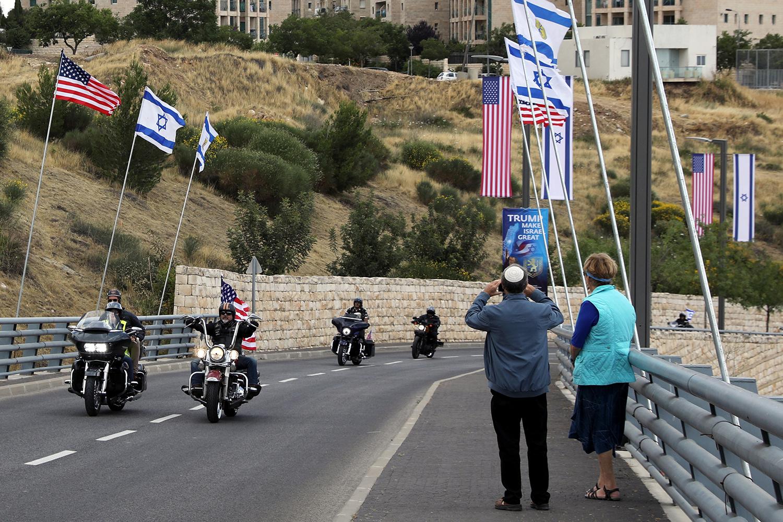Pedestres observam passagem de motociclistas nas ruas de Jerusalém com bandeiras, antes da Inauguração da embaixada americana - 13/05/2018