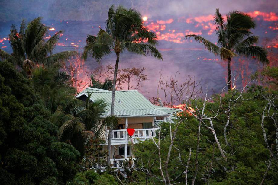Lava flui perto de uma casa nos arredores de Pahoa durante as contínuas erupções do vulcão Kilauea, no Havaí - 19/05/2018
