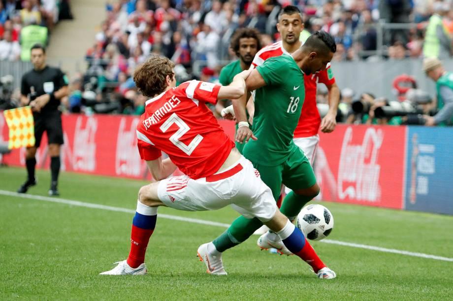 Salem Al-Dawsari, da Arábia Saudita, em ação com o russo Mario Fernandes, durante o primeiro jogo da Copa do Mundo Rússia 2018, no estádio Luzhniki, em Moscou - 14/06/2018