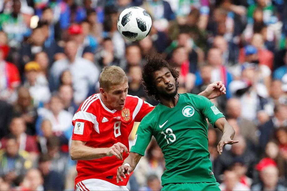 Yury Gazinsky, da Rússia, divide uma bola de cabeça com Yasser Al-Shahrani, da Arábia Saudita na partida de abertura da Copa do Mundo 2018, em Moscou - 14/06/2018