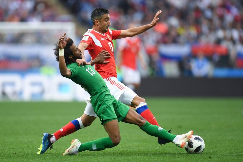 O zagueiro da Arábia Saudita, Yasser Al-Shahrani, divide uma bola com o meia russo Alexander Samedov, durante o jogo de estreia da Copa do Mundo 2018, no Estádio Luzhniki, em Moscou - 14/06/2018
