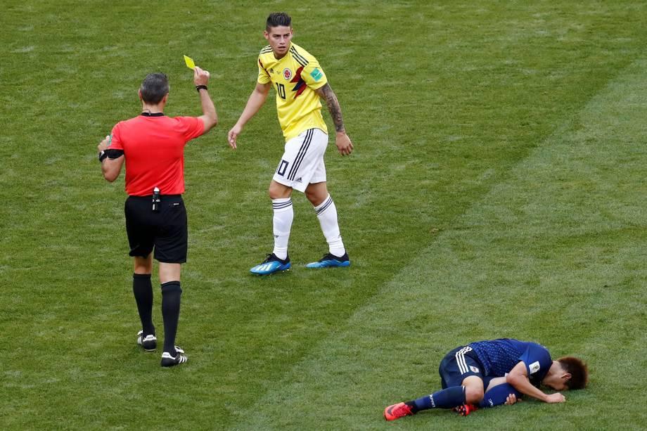 O juiz Damir Skomina mostra o cartão amarelo para James Rodriguez, da Colombia, após uma falta cometida
