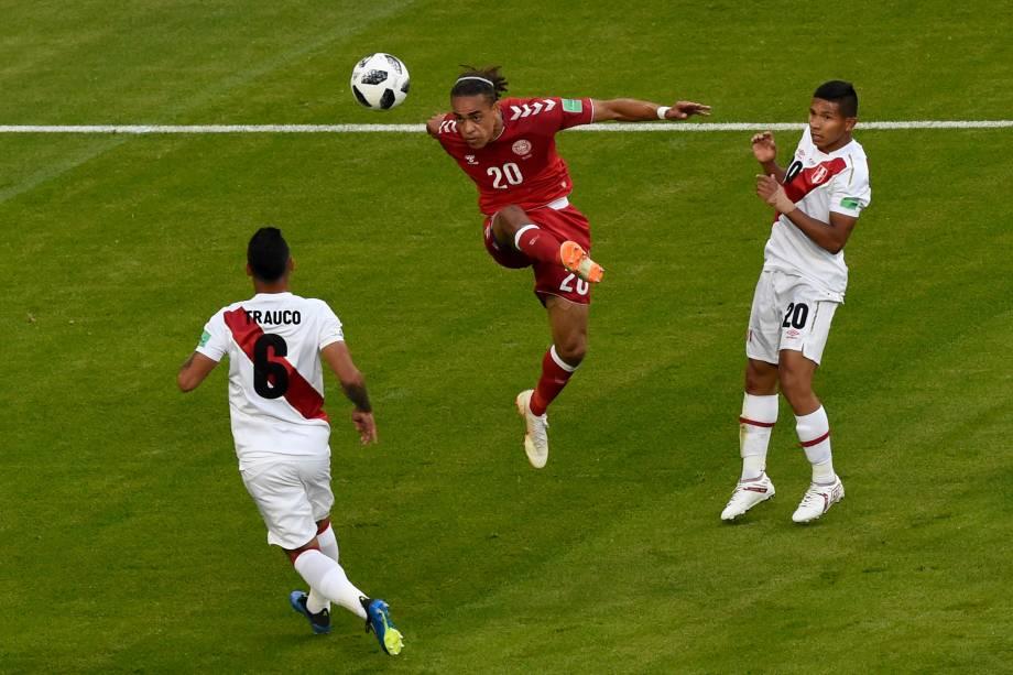 O atacante dinamarquês Yussuf Poulsen, domina a bola sob pressão do zagueiro peruano Miguel Trauco e do meia Edison Flores, durante o confronto do Grupo C entre Peru e Dinamarca