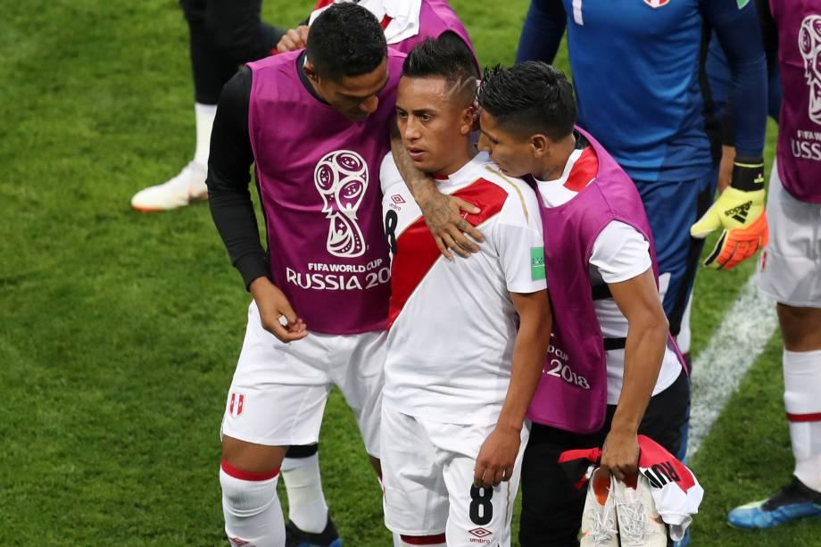 Companheiros de time consolam o peruano Christian Cueva após ter perdido um pênalti no final do primeiro tempo da partida contra a Dinamarca