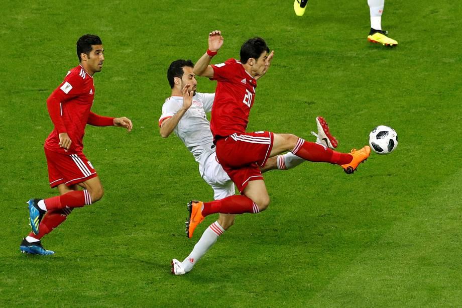 Sardar Azmoun, do Irã, disputa uma bola com o espanhol Sergio Busquets, durante a partida válida pelo Grupo B, no estádio Kazan Arena
