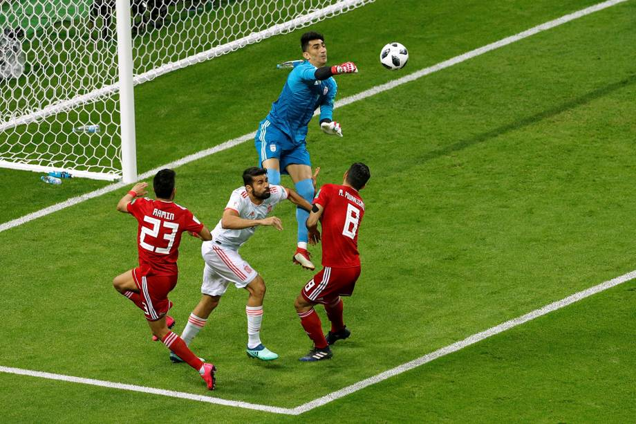 O goleiro iraniano, Alireza Beiranvand, salta sobre os jogadores para dar um soco na bola após um cruzamento da Espanha