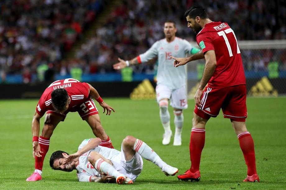 Ramin Rezaeian e Mehdi Taremi, do Irã, questionam o espanhol Isco, após uma falta cometida