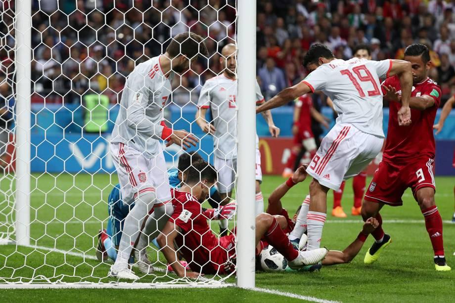 Diego Costa, da Espanha, tenta marcar um gol enquanto jogadores do Irã ficam caídos dentro da pequena área impedindo a bola de entrar
