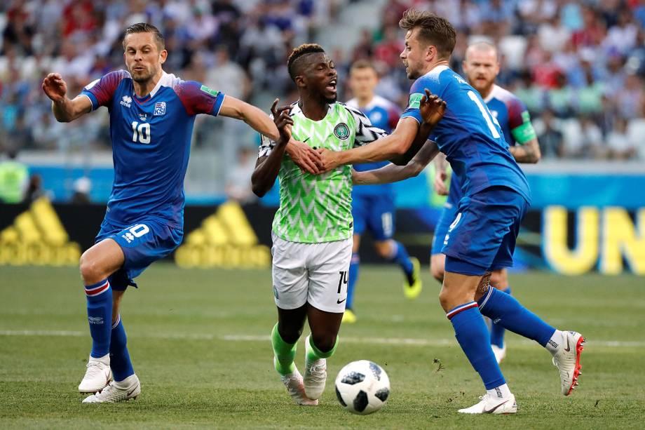 Kari Arnason e Gylfi Sigurdsson, da Islândia, seguram o nigeriano, Kelechi Iheanacho, durante o confronto do grupo D, na Arena Volgograd - 22/06/2018
