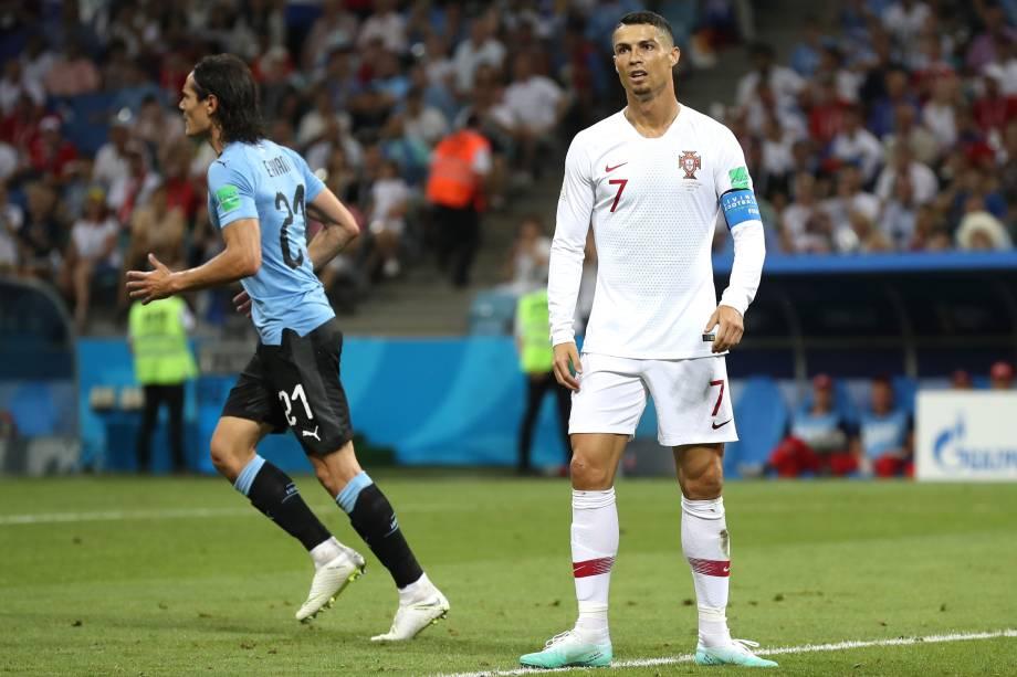 Cristiano Ronaldo reage após o gol de Edinson Cavani, do Uruguai, que sai para comemorar ao fundo - 30/06/2018