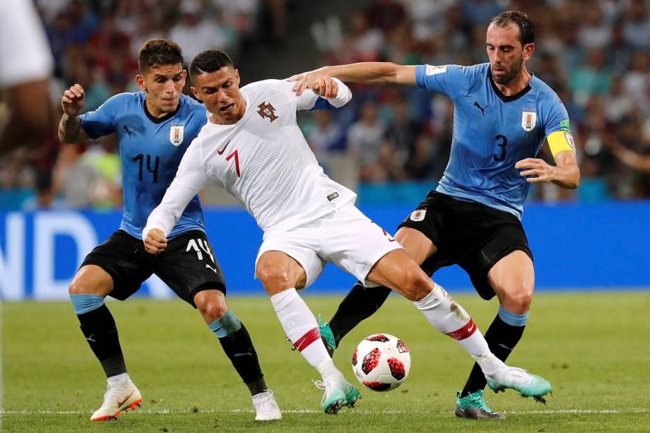 Os uruguaios Diego Godin e Lucas Torreira, realizam uma marcação dupla em Cristiano Ronaldo, de Portugal - 30/06/2018