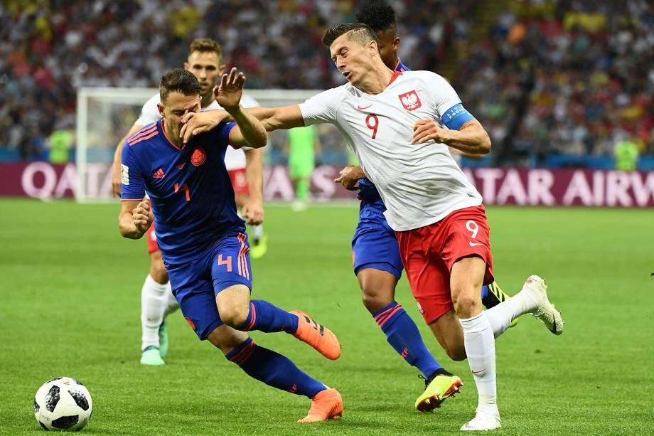 O zagueiro colombiano, Santiago Arias, é atingido pelo braço de Robert Lewandowski, da Polônia, durante uma disputa de bola - 24/06/2018