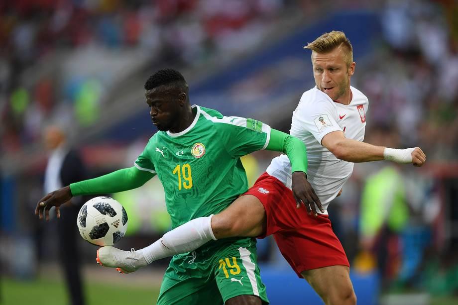 Jakub Blaszczykowski, da Polônia, divide o domínio de um lance com o senegalês Mbaye Niang