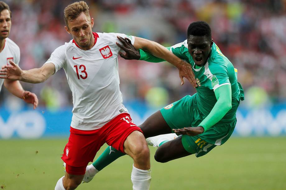 O polonês, Maciej Rybus, em ação com Ismaila Sarr, do Senegal