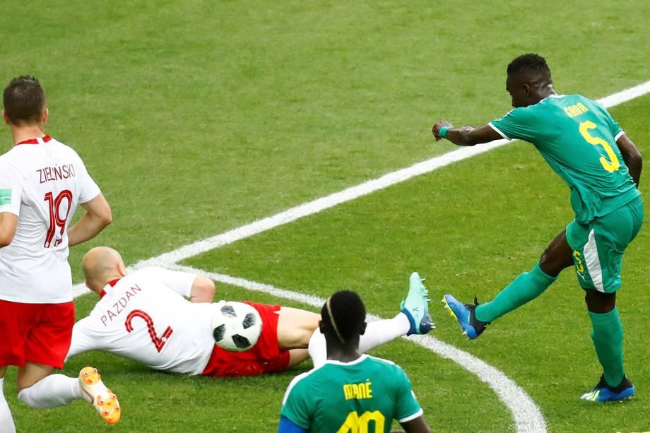 O senegalês Idrissa Gueye arrisca para o gol e acaba marcando após a bola desviar em Thiago Cionek, da Polônia