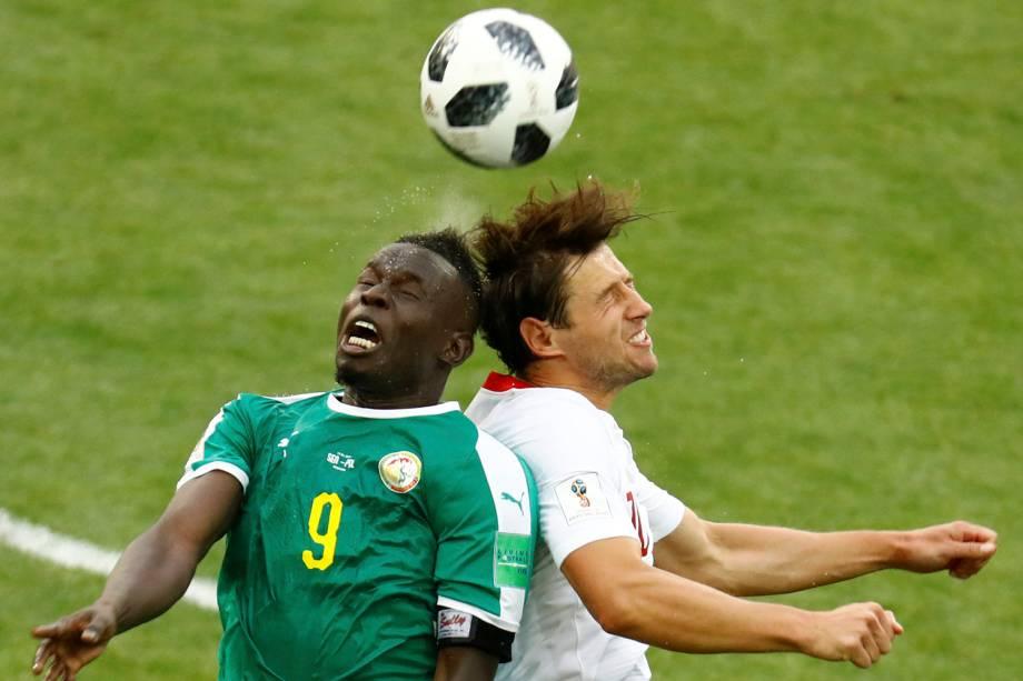 Mame Biram Diouf, do Senegal, e o polonês Grzegorz Krychowiak disputam uma bola de cabeça