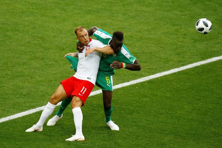 Kamil Grosicki, da Polônia, disputa uma bola com o senegalês Salif Sane