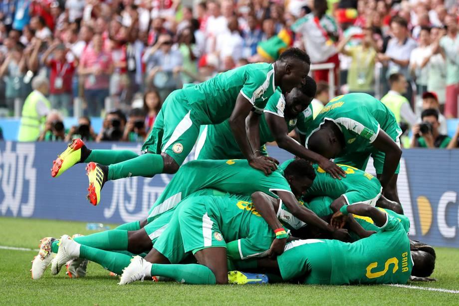 Companheiros de time pulam sobre Mbaye Niang, de Senegal, durante a comemoração do segundo gol contra a Polônia