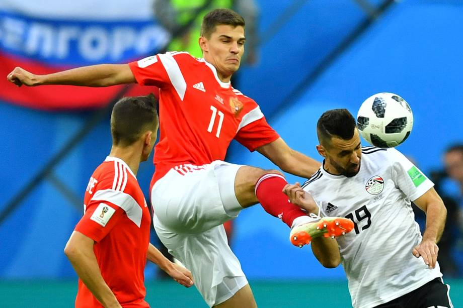 O russo Roman Zobnin chuta Mahmoud Hamdy, do Egito, durante uma tentativa de acertar a bola