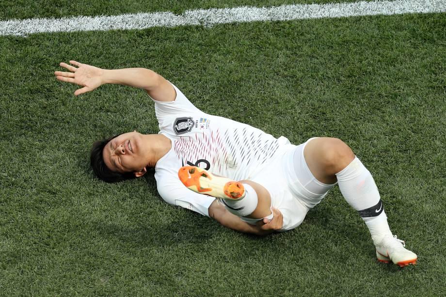 O lateral sul-coreano Park Joo-ho cai no gramado após sofrer lesão na partida contra a Suécia