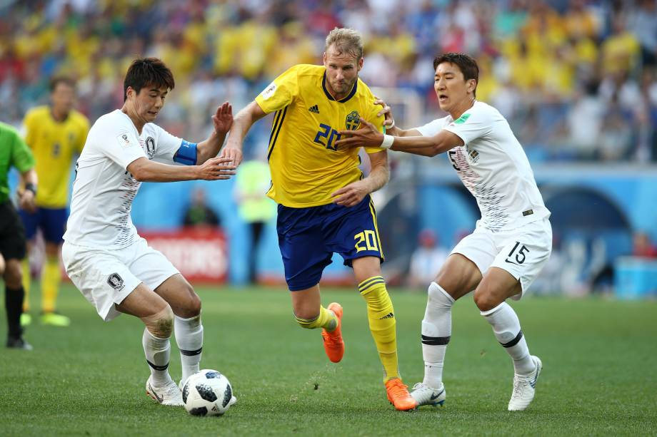 Ola Toivonen, da Suécia, escapa da marcação de Ki Sung-Yueng e Jung Woo-Young, da Coreia do Sul