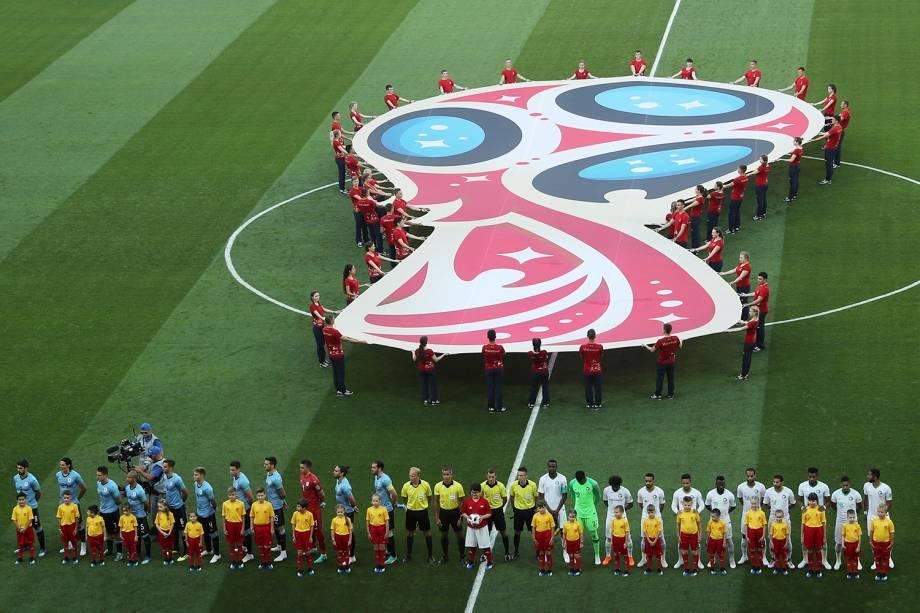 Perfiladas, as seleções de Uruguai e Arábia Saudita cantam os hinos nacionais antes do início da partida