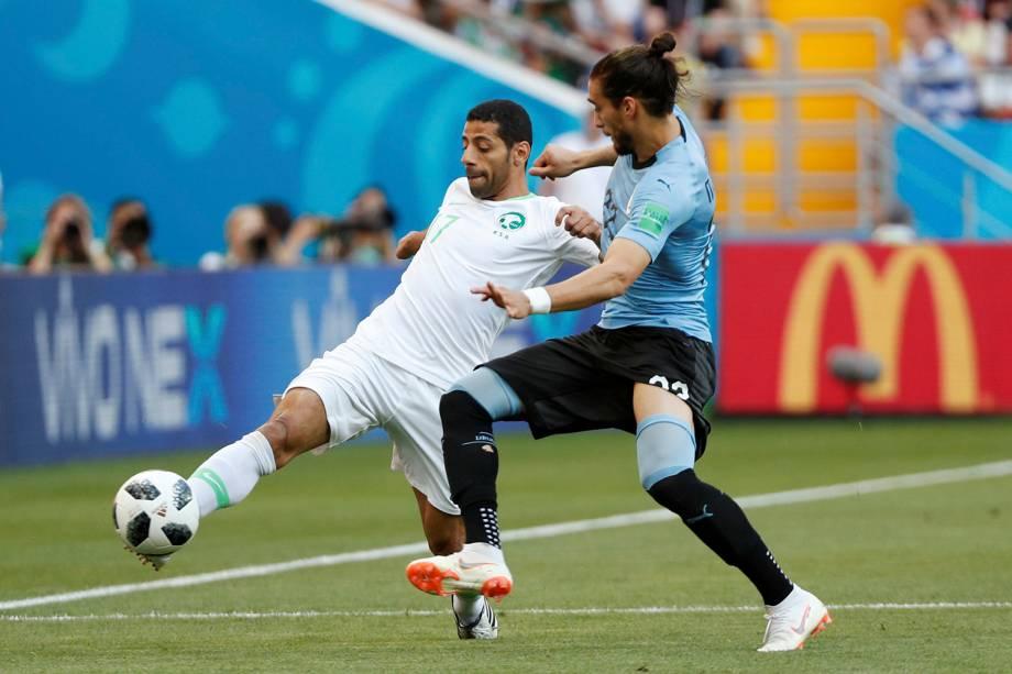 Taisir Al-Jassim, da Arábia Saudita, se estica para chutar a bola enquanto o Martin Caceres, do Uruguai, fica na marcação