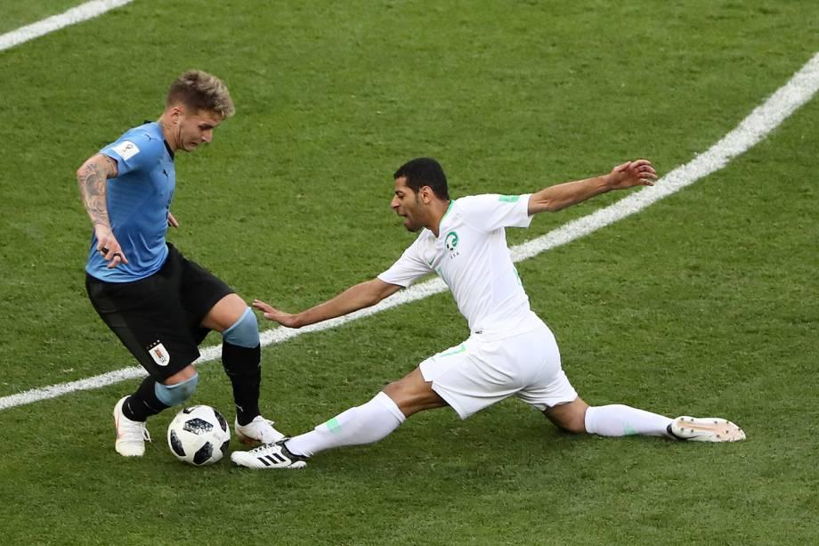 Taisir Al-Jassim, da Arábia Saudita, se lesiona ao tentar alcançar a bola sob o controle do uruguaio Guillermo Varela