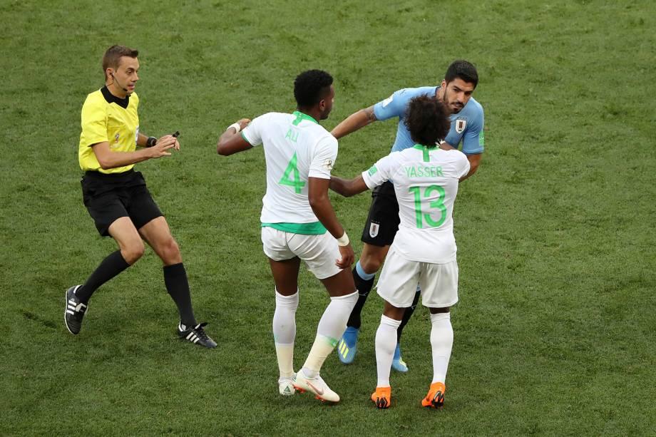 O uruguaio Luis Suarez discute com Ali Al-Bulaihi e Yasser Al-Shahrani, da Arábia Saudita, após uma falta cometida