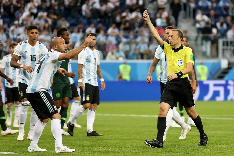 O árbitro Cuneyt Cakir mostra cartão amarelo para Javier Mascherano, durante partida entre Nigéria e Argentina - 26/06/2018