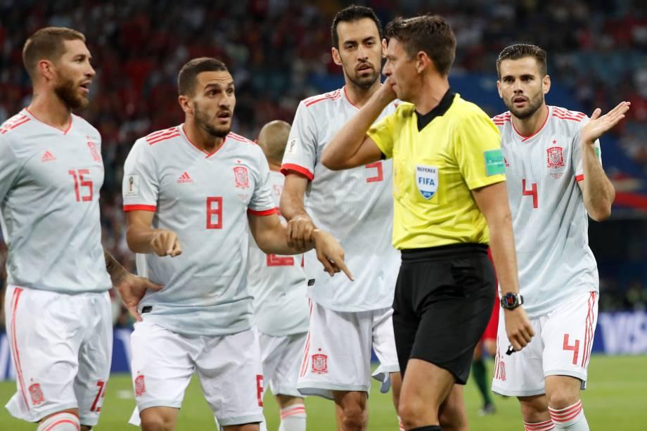 Jogadores da Espanha pressionam o árbitro Gianluca Rocchi após marcação de pênalti para Portugal