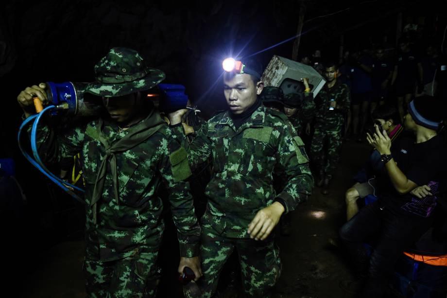 Soldados carregam equipamentos para o complexo de cavernas de Tham Luang, em busca de membros de um time de futebol sub-16 e seu treinador presos no local, na província de Chiang Rai, Tailândia - 26/06/2018