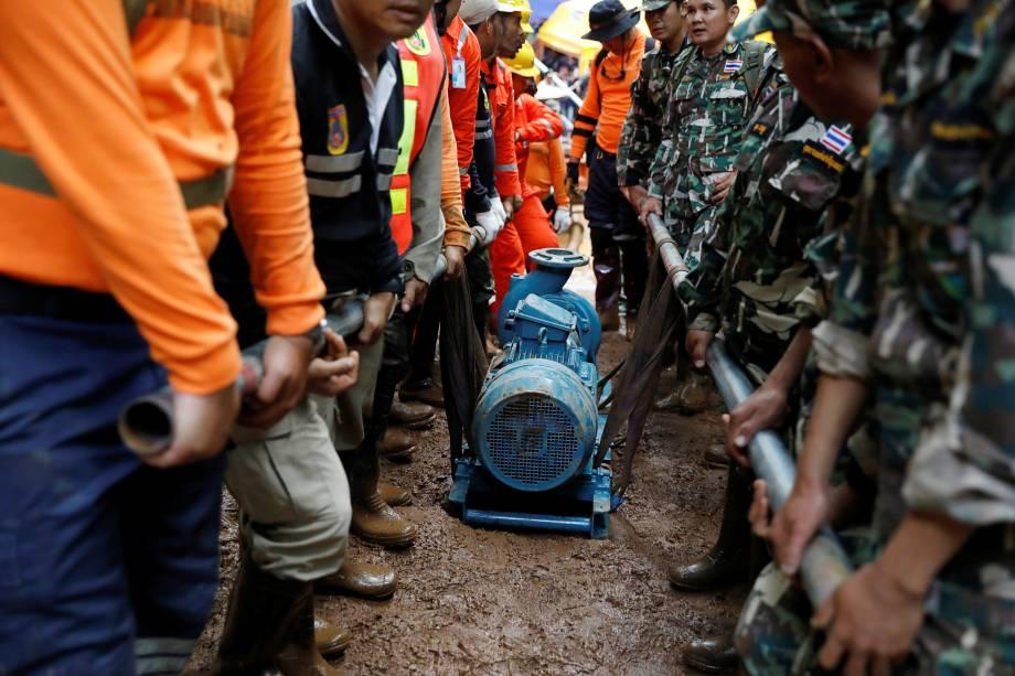 Soldados e equipes de resgate carregam uma bomba de água para o complexo de cavernas de Tham Luang durante a busca por membros de um time de futebol de crianças e seu treinador, na província de Chiang Rai, na Tailândia - 28/06/2018