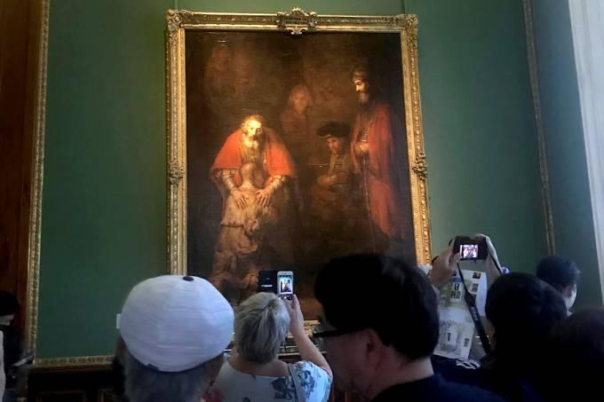 Turistas observam o quadro 'A Volta do Filho Pródigo', tela de Rembrandt de 1662, exposta no Museu Hermitage em São Petersburgo