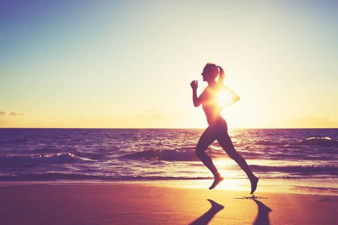 Mulher caminha em praia durante pôr do sol